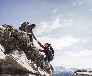 Germany, Bavaria, Oberstdorf, man helping woman climbing up rock - UUF12155