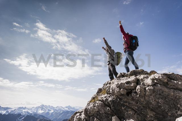 Germany, Bavaria, Oberstdorf, two hikers cheering on rock in alpine scenery - UUF12158 - Uwe Umstätter/Westend61