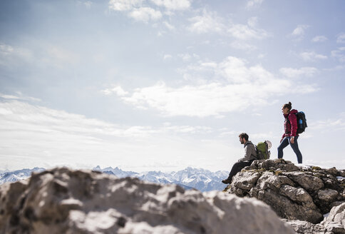 Germany, Bavaria, Oberstdorf, two hikers on rock in alpine scenery - UUF12161