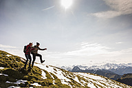 Germany, Bavaria, Oberstdorf, two hikers jumping on alpine meadow - UUF12167