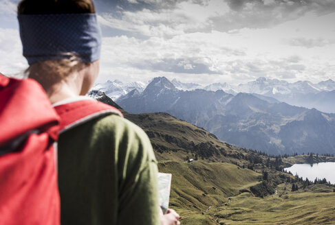 Germany, Bavaria, Oberstdorf, hiker with map in alpine scenery - UUF12173