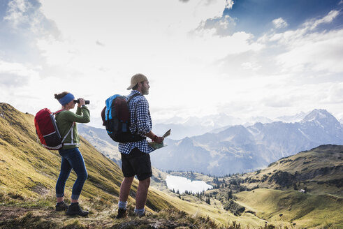 Germany, Bavaria, Oberstdorf, two hikers with map and binoculars in alpine scenery - UUF12179