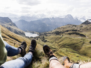 Germany, Bavaria, Oberstdorf, legs of two hikers resting in alpine scenery - UUF12182