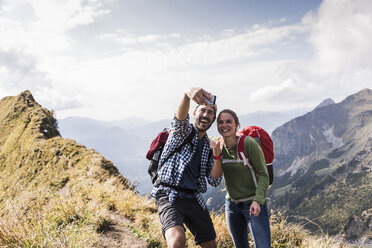 Germany, Bavaria, Oberstdorf, happy couple taking a selfie on mountain ridge - UUF12185