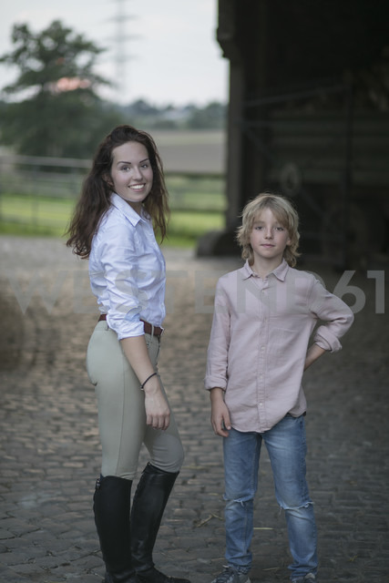 Portrait of young woman and boy on a farm - KMKF00040