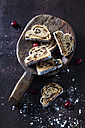Sliced Christmas Stollen with icing sugar on a wooden scoop - CSF28496