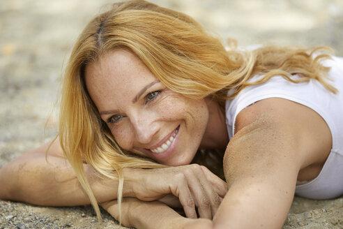 Portrait of happy strawberry blonde woman lying on the beach - PNEF00222