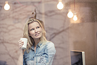 Portrait of smiling blond woman with coffee mug looking out of the window - PNEF00231