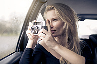 Woman sitting in car taking picture with camera - PNEF00237