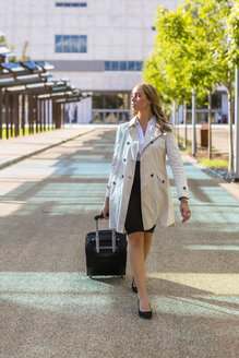 Businesswoman with suitcase wearing trench coat - MGIF00178