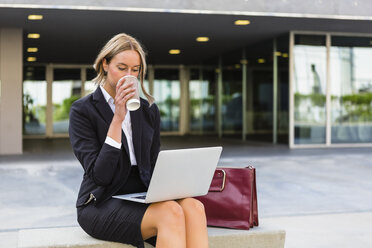 Businesswoman with fashionable leatherbag and coffee to go sitting on bench looking at laptop - MGIF00184