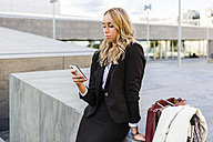 Businesswoman looking at cell phone - MGIF00187