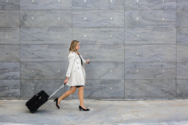 Businesswoman with suitcase wearing trench coat - MGIF00190