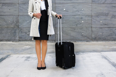 Businesswoman with suitcase wearing trench coat, partial view - MGIF00193