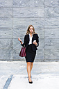 Businesswoman with fashionable leatherbag looking at cell phone - MGIF00199