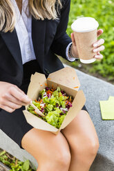 Businesswoman having lunch outdoors, partial view - MGIF00202