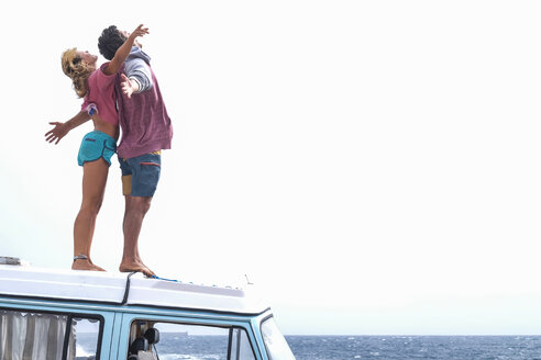 Spain, Tenerife, young couple standing on car roof enjoying freedom - SIPF01831