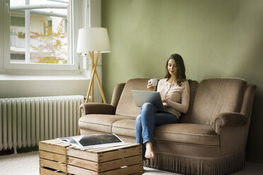 Young woman sitting on couch with cup of coffee using laptop - MOEF00186