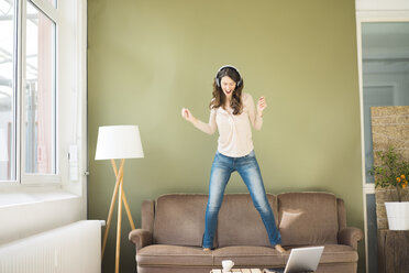 Young woman with headphones standing on couch screaming and dancing - MOEF00189