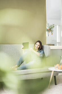 Young woman sitting on the couch taking selfie with tablet - MOEF00195