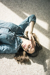 Portrait of young woman lying on carpet enjoying sunlight - MOEF00198