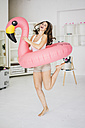 Portrait of laughing young woman dancing with flamingo swim toy at home - MOEF00210