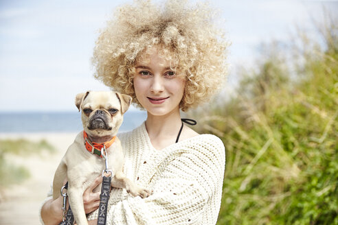 Portrait of smiling young woman holding dog on her arms - TSFF00144