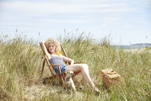 Portrait of young woman sitting on beach chair in the dunes watching something - TSFF00147