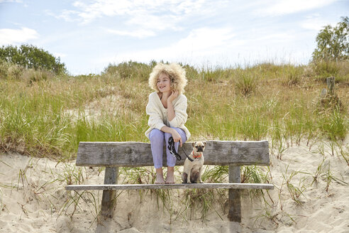Portrait of happy young woman sitting on bench in the dunes with her dog - TSFF00153