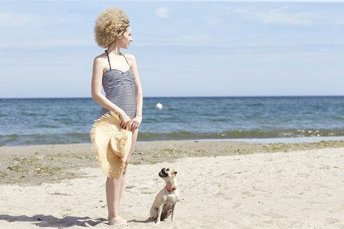 Young woman in swimsuit with straw hat and dog on the beach - TSFF00159