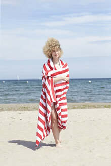 Smiling young woman wrapped in beach towel standing in front of the sea - TSFF00162