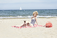 Happy young woman relaxing with her dog on the beach - TSFF00165