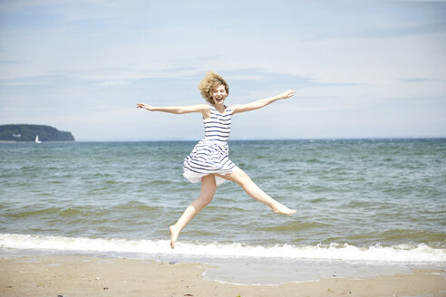 Happy young woman jumping in the air in front of the sea - TSFF00168