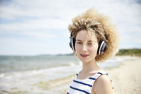Portrait of young blond woman with headphones on the beach - TSFF00171