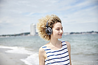 Portrait of young blond woman with headphones on the beach - TSFF00174