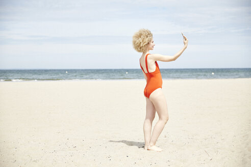 Young woman with curly blond hair taking selfie on the beach - TSFF00180