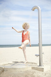 Young woman blond woman taking shower on the beach - TSFF00183