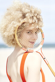 Portrait of young woman looking through reticule of tennis racket on the beach - TSFF00186