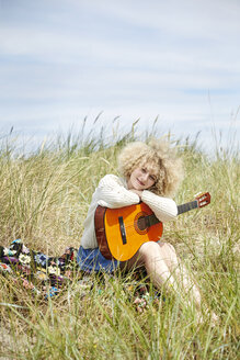 Portrait of young woman with guitar relaxing in beach dunes - TSFF00189
