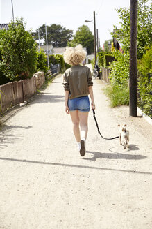 Back view of young blond woman going walkies with her dog - TSFF00195