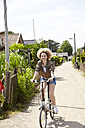 Portrait of smiling young woman riding bicycle - TSFF00198