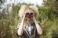 Young woman with curly hair looking through old binoculars - TSFF00201