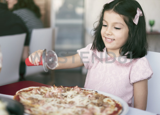 Little girl with oversized pizza in a restaurant - JASF01845