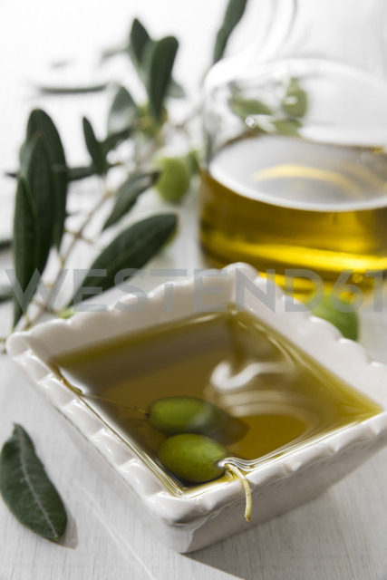 Fresh olive oil in bowl with green olives - CSTF01450