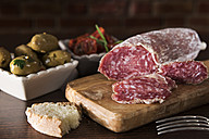 Antipasti, pickled olives, pickled tried tomato, olive bread, salami on chopping board - CSTF01456