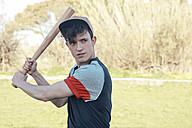 Portrait of young man with baseball bat in park - RTBF01078