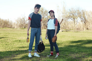 Portrait of young couple with baseball equipment in park - RTBF01081
