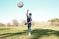 Young man throwing a baseball in park - RTBF01084