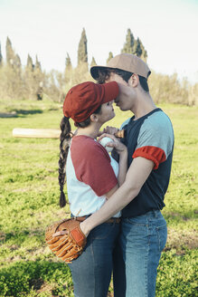 Young couple with baseball equipment kissing in park - RTBF01090