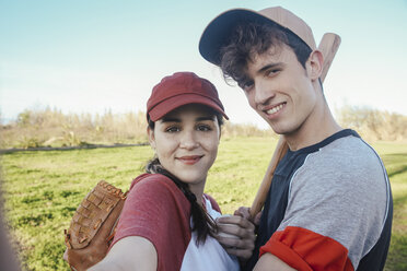 Portrait of smiling young couple with baseball equipment in park - RTBF01093